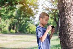 Muchacho asiático lindo joven que usa un smartphone Imagen de archivo libre de regalías