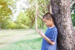 Muchacho asiático lindo joven que usa un smartphone para jugar al juego Foto de archivo