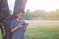 Muchacho asiático lindo joven que usa un smartphone para jugar al juego en el parque Imagen de archivo