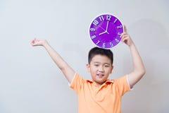 Muchacho asiático perezoso que muestra y que sostiene el reloj púrpura o violeta en stu Fotos de archivo