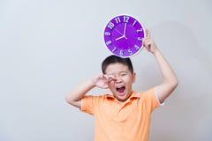 Muchacho asiático perezoso que muestra y que sostiene el reloj púrpura o violeta en stu Foto de archivo