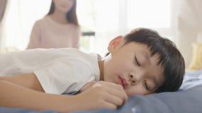 Muchacho asiático que duerme en cama por la mañana mientras que madre que se sienta en fondo Fotos de archivo libres de regalías
