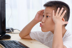 Muchacho asiático que juega al juego de la PC en casa Imagen de archivo libre de regalías