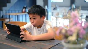 Muchacho asiático que juega al juego online con la tableta almacen de video