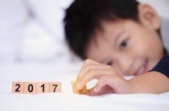Muchacho asiático que juega el texto de madera 2017 del bloque El pequeño jugar lindo del muchacho Foto de archivo libre de regalías