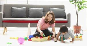 Muchacho asiático que juega los juguetes con su madre almacen de video