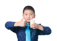 Muchacho asiático que le da los pulgares para arriba con el vidrio de leche a disposición Fotos de archivo libres de regalías