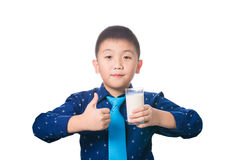 Muchacho asiático que le da los pulgares para arriba con el vidrio de leche a disposición, isola Foto de archivo libre de regalías