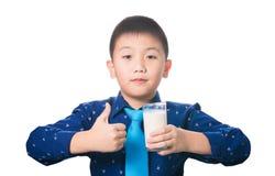 Muchacho asiático que le da los pulgares para arriba con el vidrio de leche a disposición, isola Foto de archivo