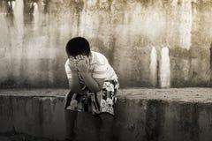 Muchacho asiático que llora solamente en la pared vieja Imagenes de archivo
