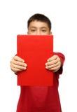 Muchacho asiático que muestra el libro rojo grande Fotografía de archivo