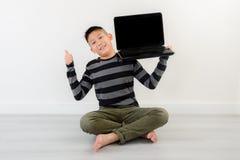 Muchacho asiático que muestra el ordenador portátil en blanco en casa Foto de archivo