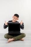 Muchacho asiático que muestra el ordenador portátil en blanco en casa Imágenes de archivo libres de regalías