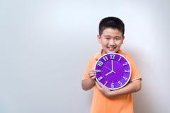 Muchacho asiático que muestra y que sostiene el reloj púrpura o violeta en el estudio s Fotos de archivo