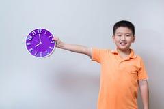 Muchacho asiático que muestra y que sostiene el reloj púrpura o violeta en el estudio s Fotos de archivo libres de regalías