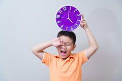 Muchacho asiático que muestra y que sostiene el reloj púrpura o violeta en el estudio s Fotografía de archivo