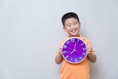 Muchacho asiático que muestra y que sostiene el reloj púrpura o violeta en el estudio s Imagen de archivo