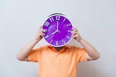 Muchacho asiático que muestra y que sostiene el reloj púrpura o violeta en el estudio s Imágenes de archivo libres de regalías