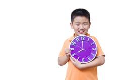 Muchacho asiático que muestra y que sostiene el reloj púrpura o violeta en el estudio s Imagenes de archivo