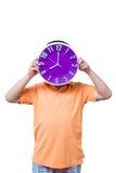 Muchacho asiático que muestra y que sostiene el reloj púrpura o violeta en el estudio s Foto de archivo