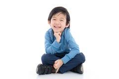 Muchacho asiático que se sienta en el fondo blanco fotos de archivo