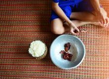 muchacho asiático que sienta y que come el desayuno con las luces anaranjadas de Foto de archivo libre de regalías