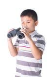 Muchacho asiático que sostiene los prismáticos, aislados en un fondo blanco Imagen de archivo