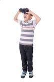 Muchacho asiático que sostiene los prismáticos, aislados en un fondo blanco Imágenes de archivo libres de regalías