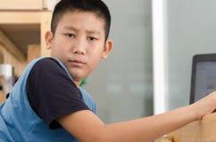 Muchacho asiático que usa el ordenador portátil en casa Imagen de archivo libre de regalías