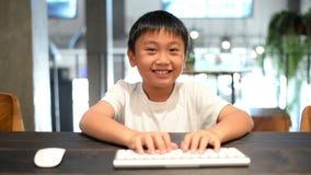 Muchacho asiático que usa el ordenador y las prensas en las llaves