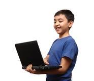Muchacho asiático sonriente con la computadora portátil Fotografía de archivo libre de regalías