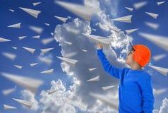 Muchacho asiático, vidrios que llevan, sombrero anaranjado y camisa azul larga Lanzar un aeroplano de papel imagen de archivo