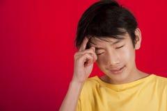 Muchacho asiático adolescente que finge pensar Foto de archivo