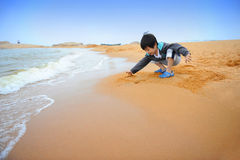 Muchacho asiático que juega en la playa Imagenes de archivo
