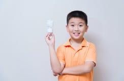 Muchacho asiático que sostiene una lámpara, lámpara ahorro de energía, Foto de archivo libre de regalías