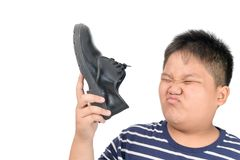 Muchacho asqueado que sostiene un par de zapatos de cuero hediondos fotos de archivo libres de regalías