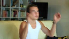 Muchacho atractivo joven del adolescente que salta en watc del sofá almacen de metraje de vídeo