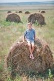 Muchacho atractivo que se sienta en un pajar y una sonrisa Fotografía de archivo libre de regalías