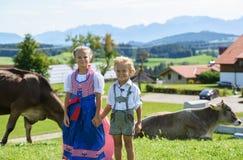 Muchacho bávaro feliz con la hermana en el prado con la vaca Montañas en fondo Fotografía de archivo