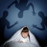 Muchacho bajo cubiertas con una linterna Imagen de archivo libre de regalías