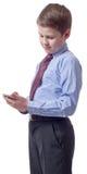 Muchacho bastante joven que mira smartphone Imagen de archivo