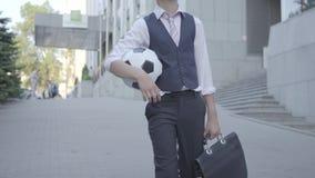 Muchacho bien vestido desconocido que camina abajo de la calle que sostiene la caja de la bola y del documento de fútbol en manos metrajes