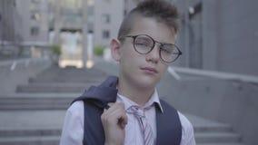 Muchacho bien vestido hermoso en la situación con gafas en la calle que mira in camera Niño serio delante de hermoso metrajes