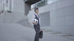 Muchacho bien vestido serio que camina abajo de la calle que sostiene la bola y el monedero de fútbol en manos Niño serio simultá almacen de metraje de vídeo