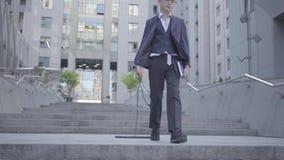 Muchacho bien vestido serio que camina abajo de la calle que tira del teclado a lo largo de los pasos, sosteniéndolo por el alamb almacen de video