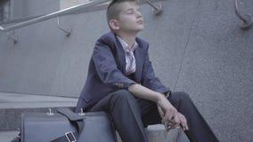 Muchacho bien vestido triste que se sienta en las escaleras en la calle El muchacho está cansado y quiere ser apenas un niño Niño metrajes