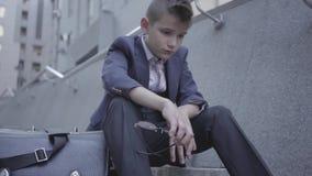 Muchacho bien vestido triste que se sienta en las escaleras en la calle, monedero viejo cerca de él El muchacho que saca los vidr almacen de metraje de vídeo