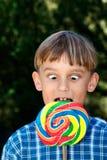 Muchacho bizco que come el lollipop Imagen de archivo libre de regalías