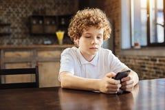 Muchacho cabelludo de la castaña tranquila que elige música en el teléfono Fotos de archivo libres de regalías