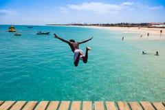 Muchacho caboverdiano adolescente que salta en el agua de la turquesa de Sant Imagen de archivo